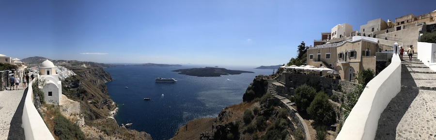 A panoramic image of the cliffside walking path between Fira and Firostefani on Santorini Island Greece
