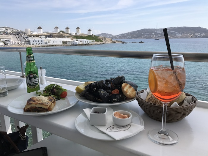A view of Mykonos windmills while enjoying a delicious snack