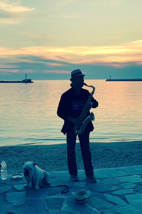 A saxophone player and his old dog in Mykonos sunset